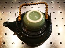 Small black teapot, handle with bark to reduce heat holding time. And a green cup for tea is on the teapot. It is located on a stainless steel sieve, with Royalty Free Stock Images
