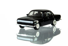 Small black toy car. Isolated on white with reflection and shallow depth of field stock image