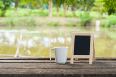 Small blackboard on rustic wood table Stock Images