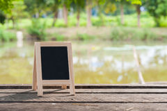 Small blackboard on rustic wood table Royalty Free Stock Images
