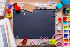 Small blackboard surrounded with varioius stationaries with empt Stock Images