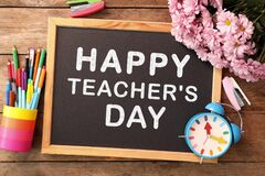 Small blackboard with text Happy Teacher`s Day, stationery and flowers on wooden table, top view