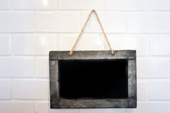 Small blackboard on white brick wall Royalty Free Stock Photo