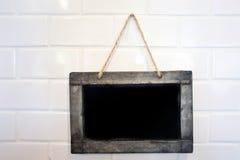 Small blackboard on white brick wall. Small blackboard hang on white brick wall Royalty Free Stock Photo