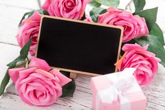 Small blank chalkboard for Valentine`s, mother or woman day. Background with pink roses. Royalty Free Stock Photos