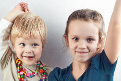 Small blond boy and girl pull hands up stock photography