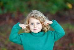 Small blond child with green jersey imagining something. In the field Stock Photography