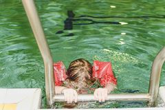 Small blond girl with armband floats in swimming pool. Child learns to swimm. Girl goes up on ladder in public pool. Stock Photos