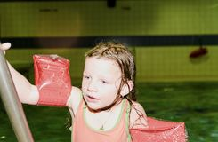 Small blond girl with armband floats in swimming pool. Child learns to swimm. Girl goes up on ladder in public pool. Stock Photography