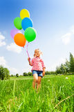 Small blond girl with many balloons in park Royalty Free Stock Image
