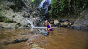 Small Blond Girl Plays in Water near Mountain Waterfall. Little blonde girl in blue swimsuit plays in clean transparent water by mountain waterfall among rocks stock video