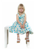 Small blond girl sits on white chair Stock Photography