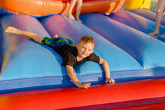 Small blonde boy lying on bouncy castle Stock Images