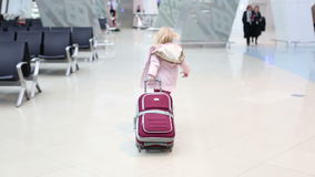 Small blonde girl in a pink winter coat with red suitcase walking across waiting hall in the airport. stock video
