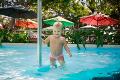 Small blonde girl smiles holds pole in shallow water of pool. Small blonde girl smiles and holds pole in shallow water of hotel swimming pool against colourful stock photography