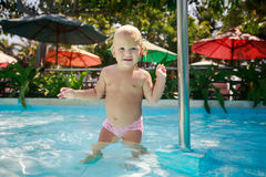 Small blonde girl smiles holds pole in shallow water of pool Stock Photo