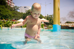 Small blonde girl smiles plays in shallow hotel swimming pool Royalty Free Stock Photo