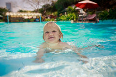 Small blonde girl stands looks slyly in shallow water of pool Stock Image