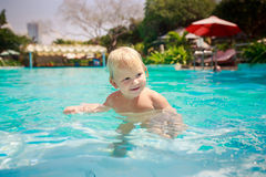 Small blonde girl stands looks slyly in shallow water of pool Royalty Free Stock Photos