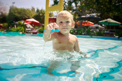 Small blonde girl stands looks in transparent water of pool Royalty Free Stock Photo