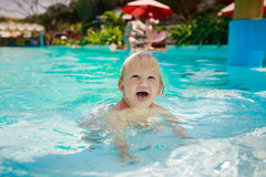 Small blonde girl stands screws up eyes in shallow pool water Stock Image