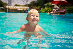 Small blonde girl stands screws up eyes in shallow pool water Royalty Free Stock Photography