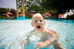 small blonde girl swims cries with joy in water of pool Stock Photos