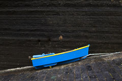 Small Blue Boat. A little blue boat tied up on a steep road with dark stone backdrop Stock Photo