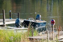 Small blue boat docked at wooded dock stock images