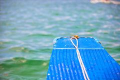 Small blue boat in open sea on desert island Stock Photography