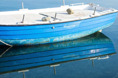 Small Blue Boat Reflected in Water Royalty Free Stock Photography
