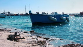 A small blue boat is rocked by the gentle waves of a turquoise sea. A small blue boat is rocked by the gentle waves of the turquoise mediterranean sea, bathing stock video footage