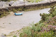 Small blue boat. Moored in the middle of the mouth of a river Stock Photos