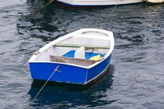 Small blue boat. Moored in a sea port Stock Photos