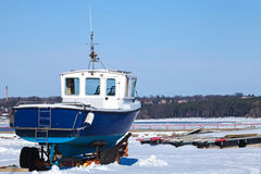 Small blue boat on the snowy sea coast Stock Photography