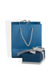 Small blue box tied with a silver ribbon and gift paper-bag as a set.  Stock Image