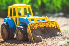 Toy tractor in the sand stock images