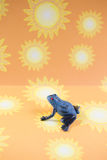 Small Blue Frog Sunshine Background. Small blue plastic frog on sunny yellow and orange sunshine paper background Stock Images
