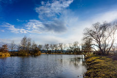 Small blue lake under the clear sky with clouds. Royalty Free Stock Photos