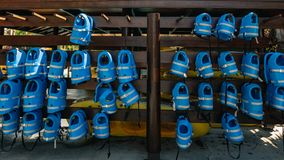 Small blue life jackets for kids are hanging in row at poo Stock Image