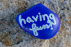 Small blue painted rock with words Having Fun!. Small blue painted rock with a message painted in white letters stating `having fun!`  Letters have blue dots Royalty Free Stock Photo