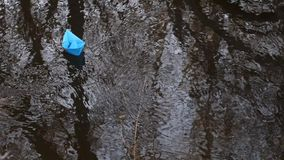 Small blue paper boat floats with stream of transparent river in the autumn park. Small blue paper boat floats with stream of transparent river in autumn park stock video