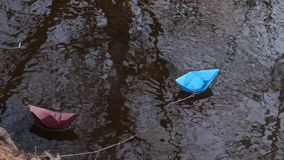 Small blue paper boat flowing with a stream of transparent river, reflected in it of trees. Small blue paper boat flowing with stream of transparent river stock video footage