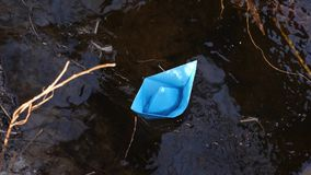 Small blue paper boat flowing with a stream of transparent river, reflected in it of trees. close up. Small blue paper boat flowing with stream of transparent stock video footage