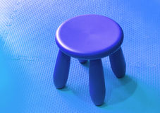 Small blue plastic stool for kids isolated on cryans soft floor Stock Photos