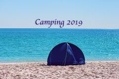Camping 2019 Text - A Small Blue Shade Tent On A White Silica Sand Beach In Whitsund. A small blue round collapsible shade tent on the white silica sand of stock images