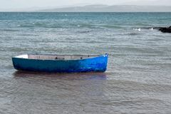 Small blue rowing boat moored in the sea royalty free stock photos