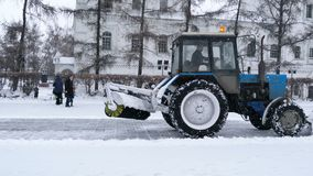 Small blue snow plow removes snow on the street in Irkutsk stock footage