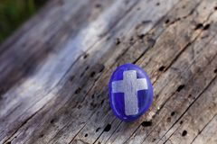 Small blue stone with a silver cross painted on front Royalty Free Stock Image