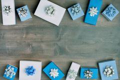 Small blue and white gift boxes with beautiful silver bows on a dark wooden background. Christmas composition, beautiful stock photos